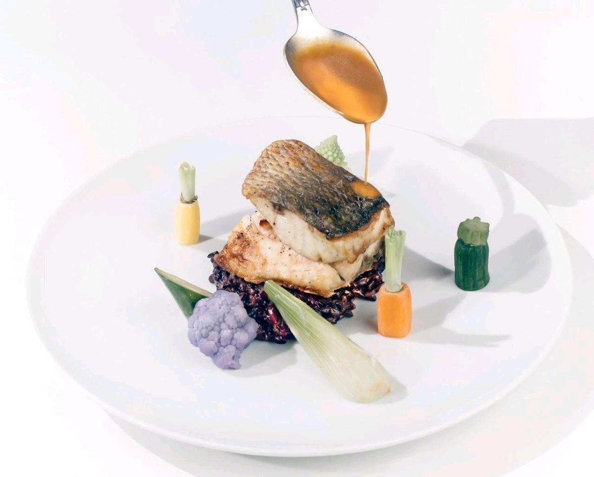 Λαυράκι με μαύρο ριζότο, ζεστό ταρτάρ γαρίδας και σάλτσα αστακού.